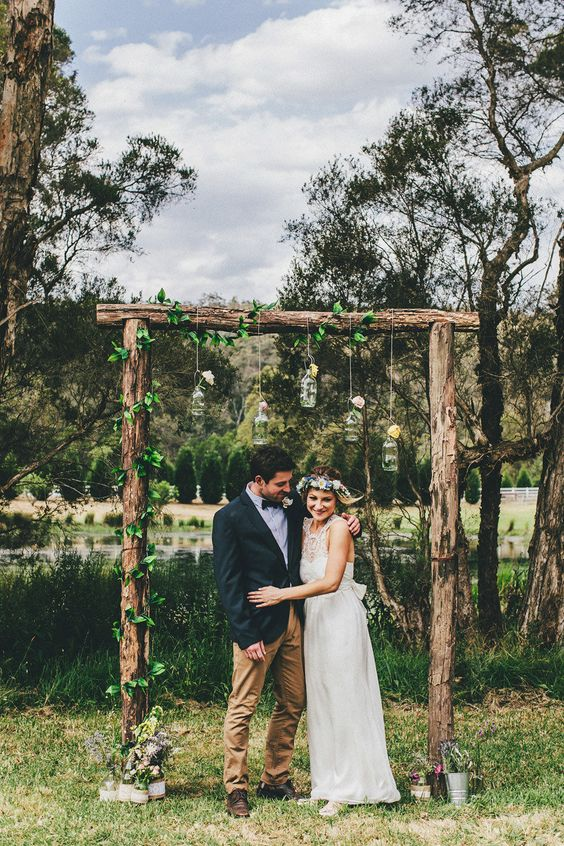 a rustic wedding arch with fresh greenery and some blooms in bottles hanging down for a summer or spring wedding