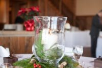 19 a simple rustic Christmas centerpiece of a wood slice, evergreens, berries, pinecones and candle lanterns