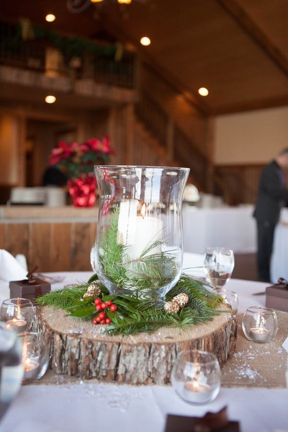 a simple rustic Christmas centerpiece of a wood slice, evergreens, berries, pinecones and candle lanterns