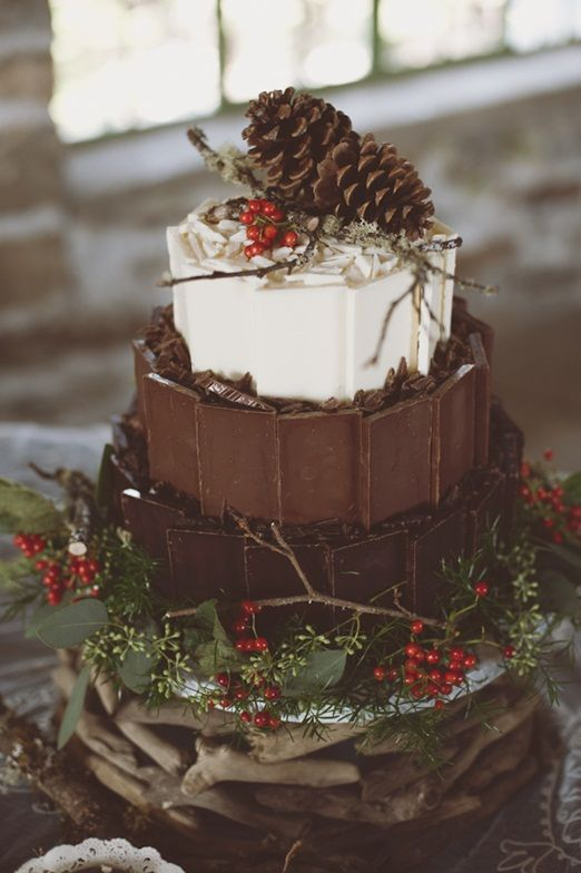 a woodland inspired Christmas wedding cake with dark, milk and white chocolate topped with berries, twigs and pinecones