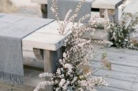 19 grey fringe throws on the benches plus white blooms for wedding aisle decor, so frozen-like