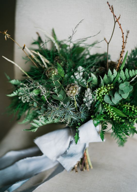 a catchy foliage and greenery wedding bouquet with berries and evergreens for a non floral winter wedding