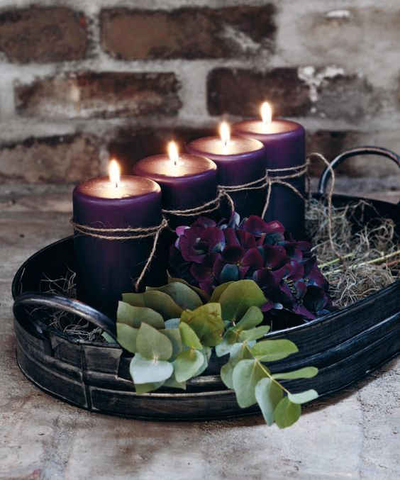 a natural winter Nordic wedding centerpiece of a tin bowl, purple blooms and candles with twine, eucalyptus for a fresh touch