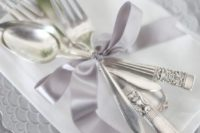20 a silver place setting with a print, silver cutlery and a lilac ribbon for a sophiticated and chic look