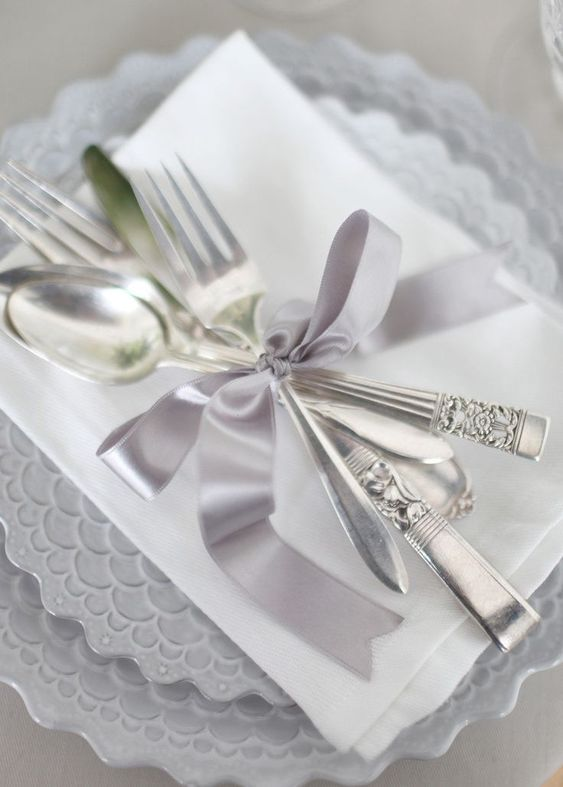 a silver place setting with a print, silver cutlery and a lilac ribbon for a sophiticated and chic look