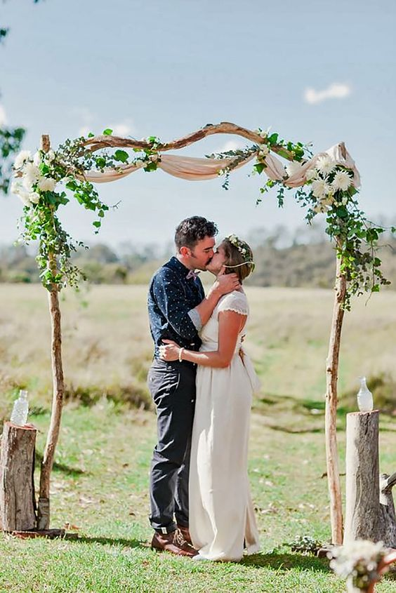 a simple and natural wedding arch of branches decorated with airy fabric, greenery and white blooms plus stumps around