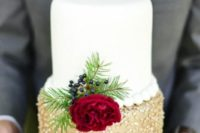 20 an elegant wedding cake features a white and a gold tier with polka dots and is decorated with a red bloom, berries and evergreens