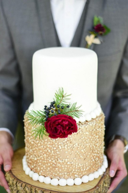 an elegant wedding cake features a white and a gold tier with polka dots and is decorated with a red bloom, berries and evergreens