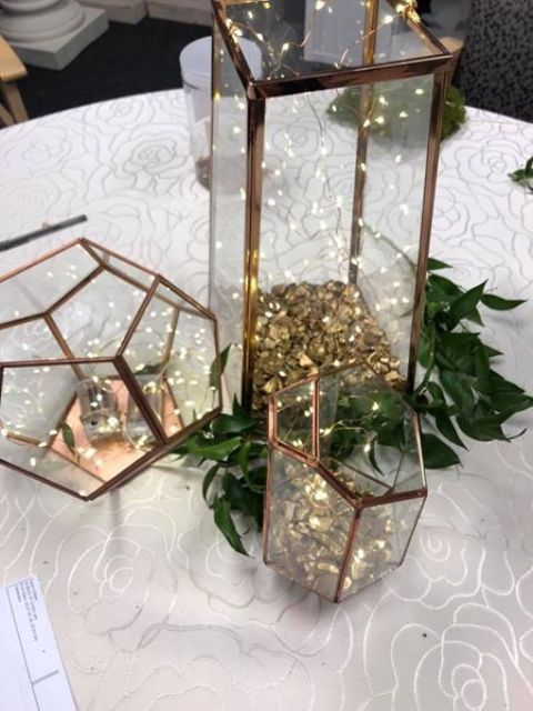 copper terrariums with LEDs and greenery around for a Christmas centerpiece, such decor always creates a mood