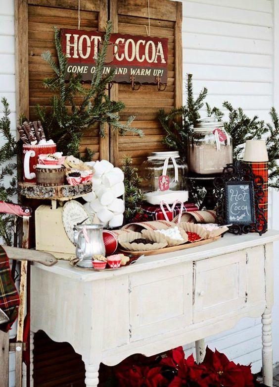 a cozy vintage hot cocoa bar made with a sideboard, decorated with evergreens and plaids
