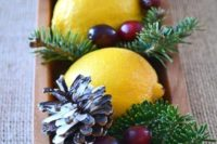 21 a fresh and modern take on traditional Christmas centerpieces of a wooden bowl, evergreens, cranberries, lemons and pinecones