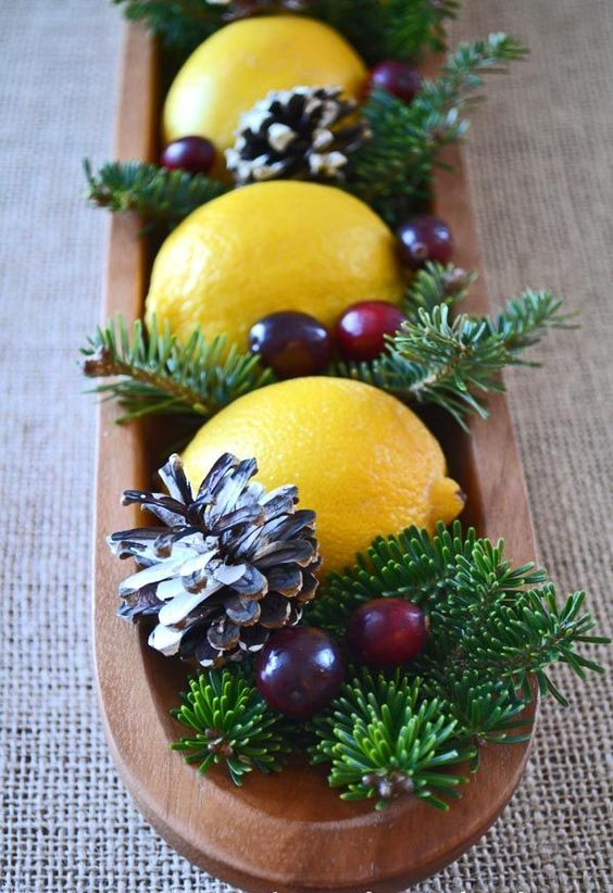 a fresh and modern take on traditional Christmas centerpieces of a wooden bowl, evergreens, cranberries, lemons and pinecones