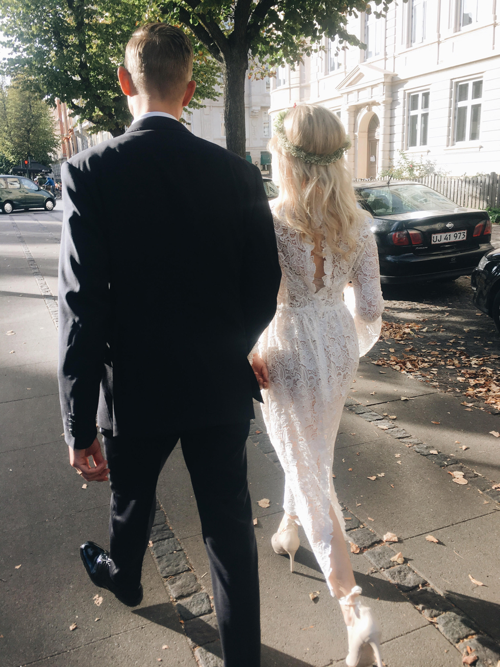 a midi boho lace fitting wedding dress with a slit on the back, long sleeves and a cutout