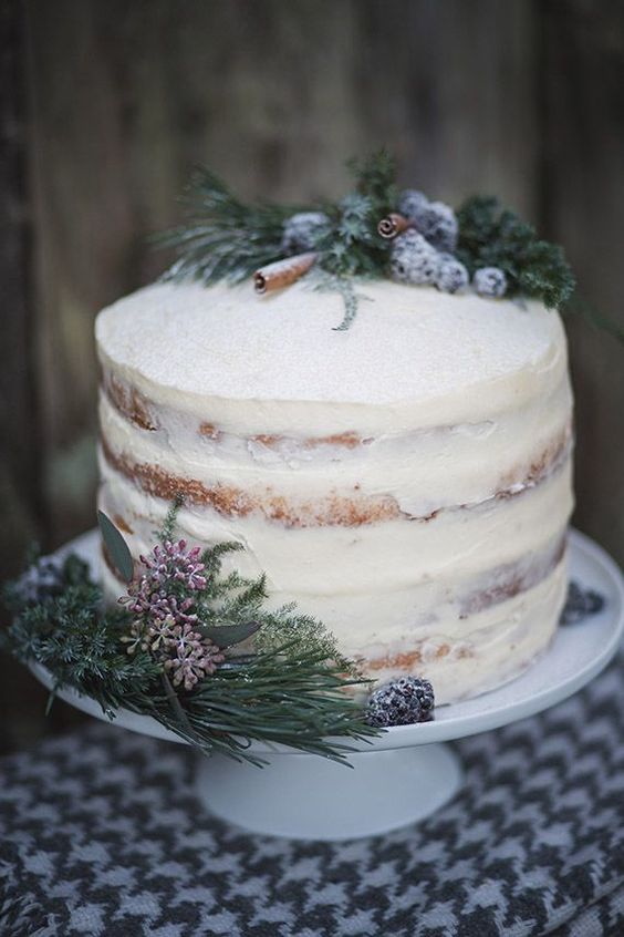 a semi-naked winter wedding cake topped with evergreens, sugared berries, cinnamon sticks and blooms for a Nordic wedding