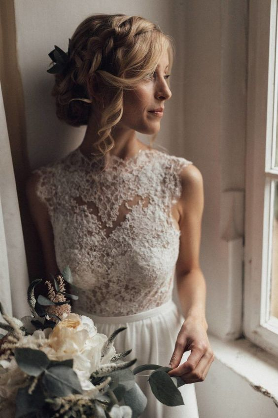a side braided wavy updo with locks down and some fresh blooms and greenery is great for a boho bride in any season