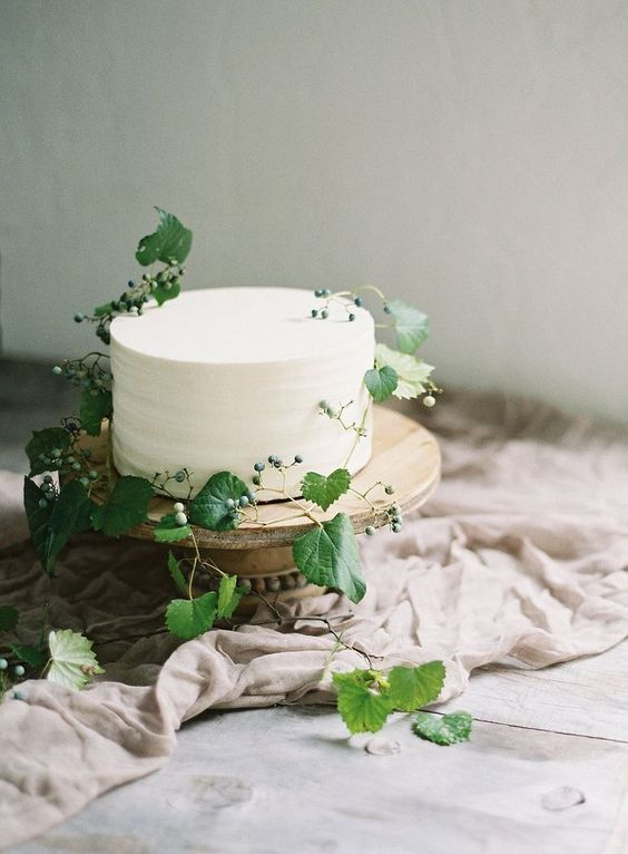 a simple and natural white wedding cake decorated with fresh greenery and berries for a delicate Nordic spring wedding