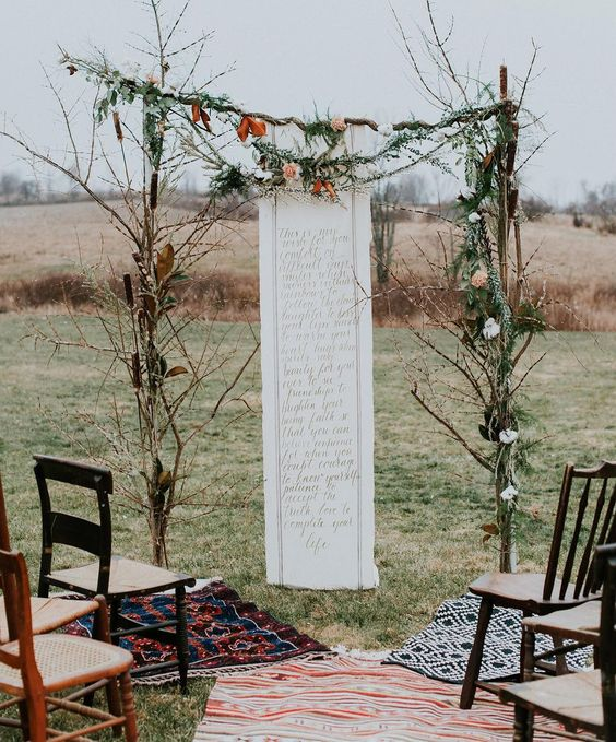 a simple boho winter wedding arch of branches, foliage and blooms with a romantic text handwritten