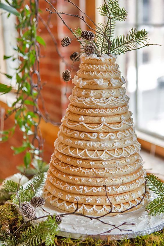 a gorgeous kransakaka topped with evergreens and pinecones and sugar patterns for a winter wedding