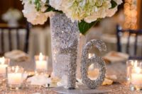 22 a silver sequin tablecloth, a silver sequin vase and a table number plus white blooms is winter classics