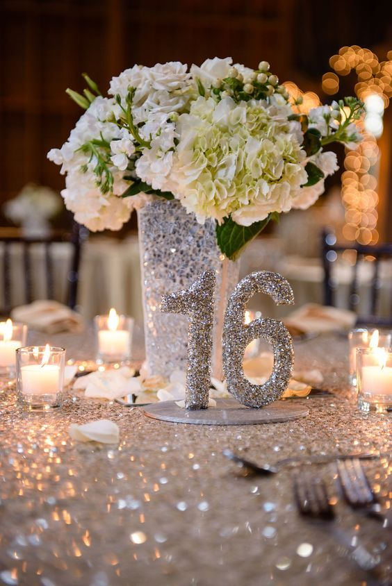 a silver sequin tablecloth, a silver sequin vase and a table number plus white blooms is winter classics