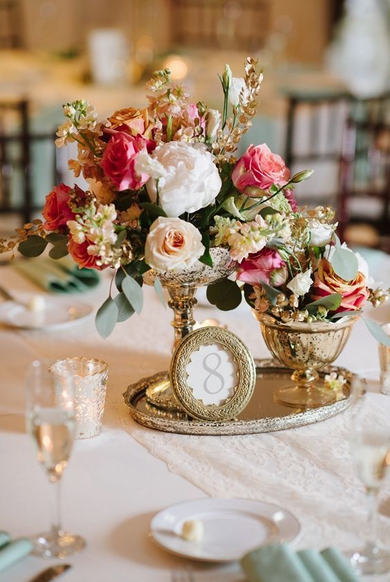 a vintage-inspired centerpiece of a gold tray, a picture frame, a duo of vases with blooms for a stunning vintage wedding