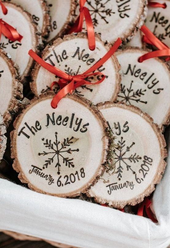 cool wood slice ornament with the wedding date and names burnt on them and a red bow