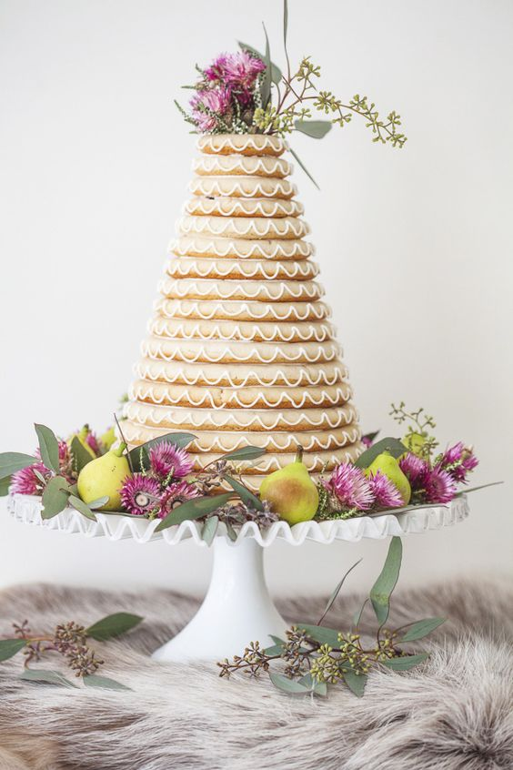 a kransekake topped with blooms and greenery and displayed on a stand with fruits, blooms and greenery