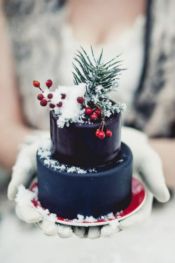a mini Christmas wedding cake in navy and deep purple, topped with berries and evergreens to make a statement with color