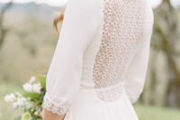 23 a plain wedding dress with a highlighted waist, long sleeves, a lace back and a lace trim on the sleeves for a romantic touch