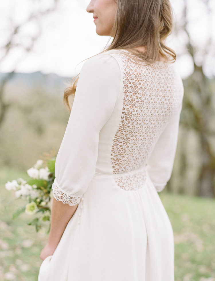 a plain wedding dress with a highlighted waist, long sleeves, a lace back and a lace trim on the sleeves for a romantic touch