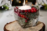 23 a rustic Christmas centerpiece of a wood slice, a glass jar with cranberries and a floating candle is easy to DIY