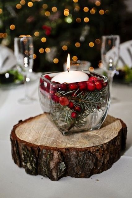 a rustic Christmas centerpiece of a wood slice, a glass jar with cranberries and a floating candle is easy to DIY