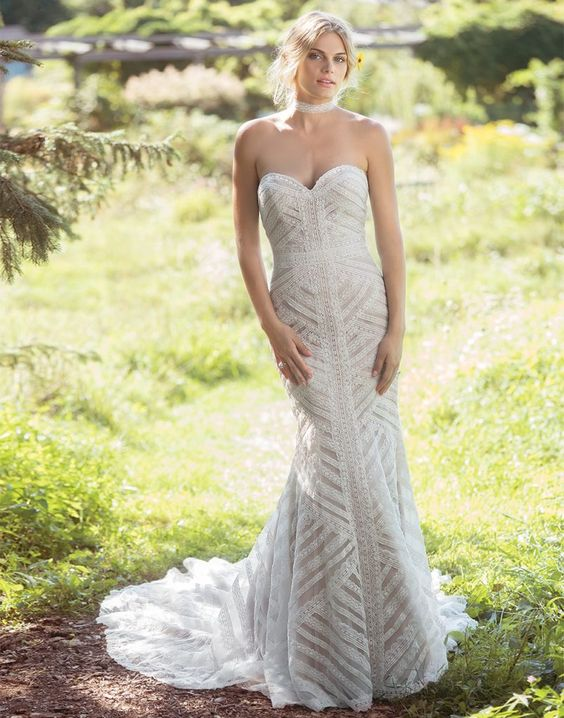 a strapless mermaid wedding dress with a geometric pattern, embellishments and a train for a very romantic bride
