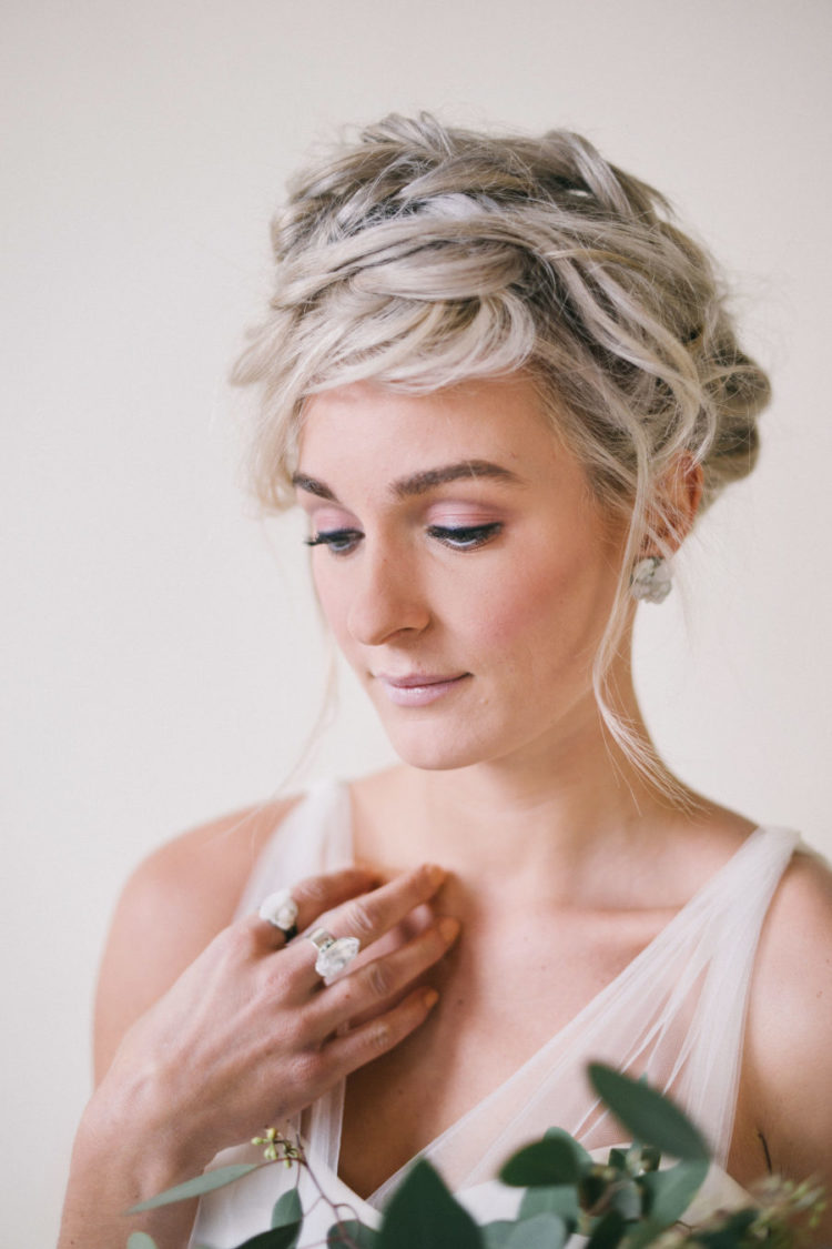a super messy braided wedding updo with some locks down is a fit for both a minimalist or boho Scandinavian bride