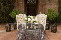 23 a sweetheart table covered with a silver sequin tablecloth and with a white bloom centerpiece