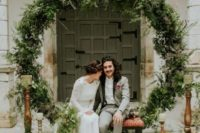 23 a trendy wedding backdrop of an oversized greenery wreath and lots of candles around