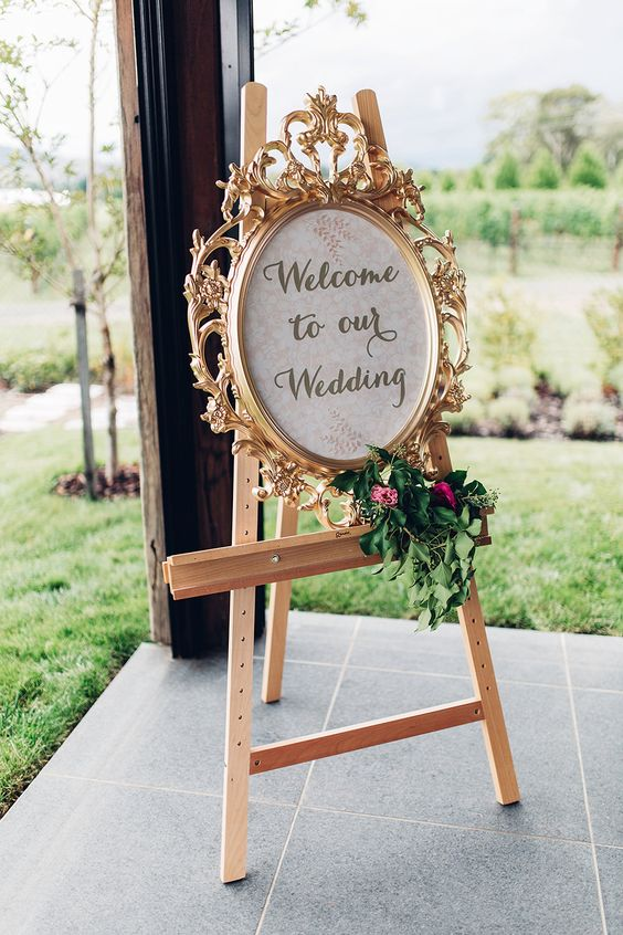 a vintage gold frame decorated with greenery and blooms and placed on an easel is a chic and sophisticated idea