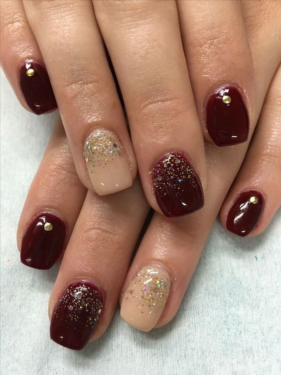 burgundy nails with rhinestones and beige nails with glitter for a bright festive manicure