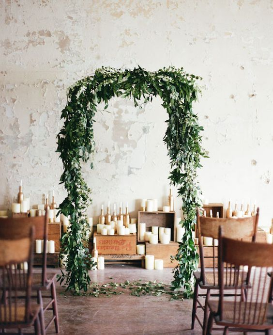 a greenery wedding arch and lots of candles will make your indoor location look like outdoors