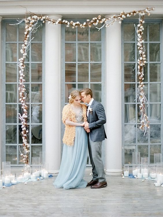 a hanging cotton garland forms an arch and large glass candle holders give a cozy feel for a winter wedding ceremony