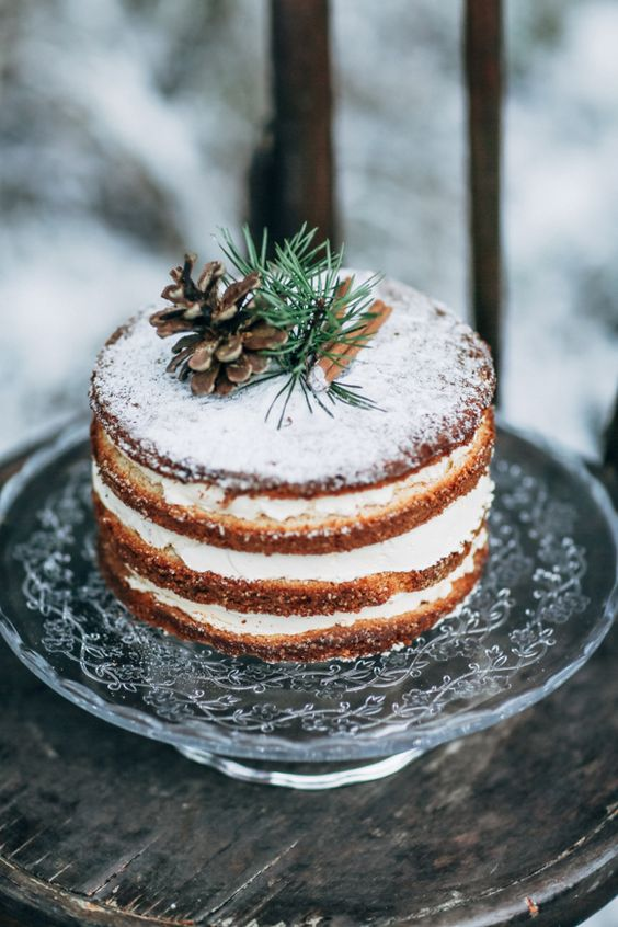 a naked Scandinavian winter wedding cake topped with cinnamon sticks, evergreens and a pinecone is a simple and cute idea