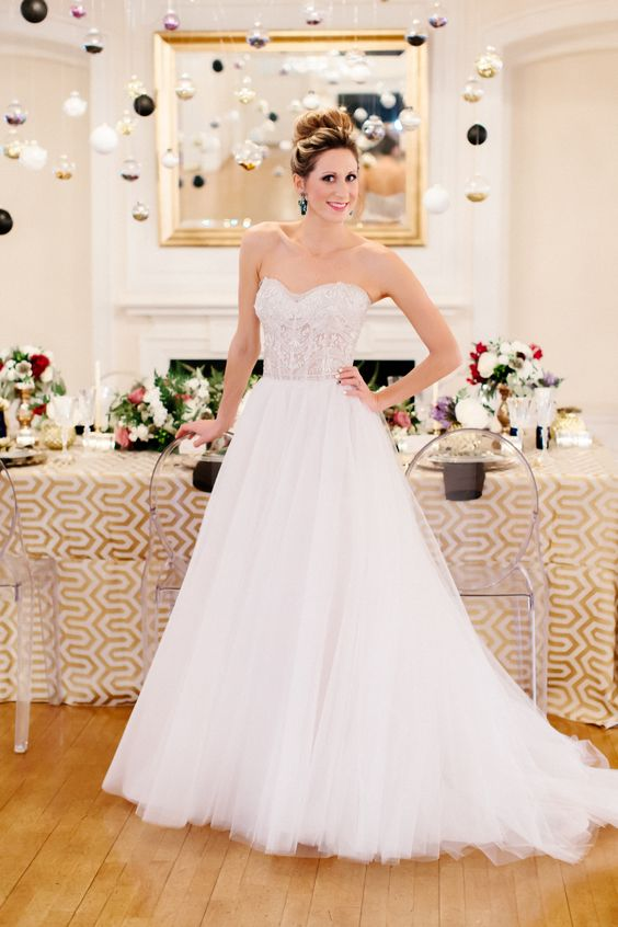 a strapless A-line wedding dress with a fully embellished bodice and a layered skirt with a train