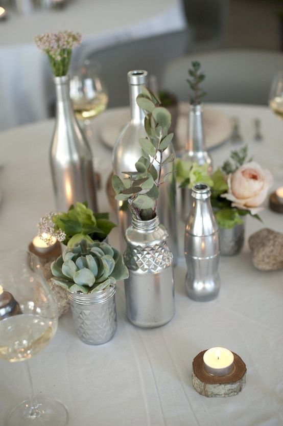 silver jars and bottles as vases for some herbs and blooms are great to compose a chic wedding centerpiece