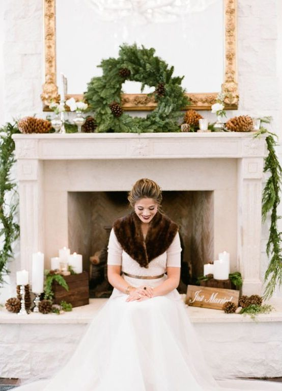 a cool winter fireplace decorated with evergreens and pinecones plus candles and a bride by it