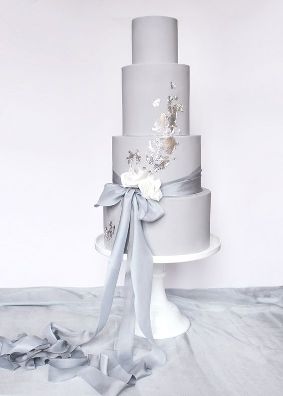 a dove grey wedding cake with a grey ribbon, white blooms and silver leaf decor for a trendy touch