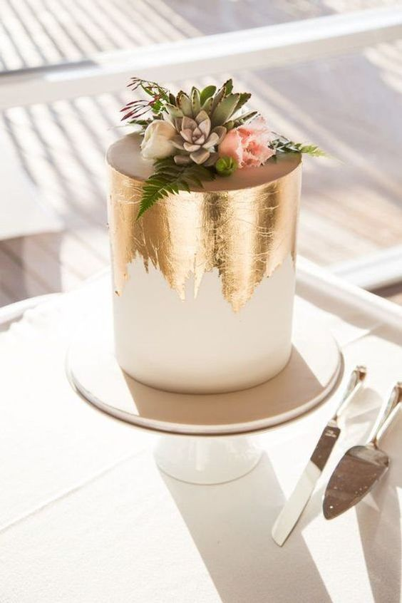 a modern wedding cake in white with gold leaf, blooms and succulents on top is a very trendy option to try