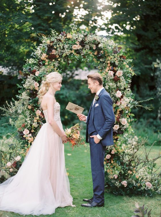 a moody wedding arch with deep purple, burgundy and blush blooms and lots of foliage for a summer wedding