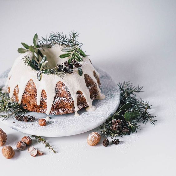 a traditional bundt wedding cake with white chocolate dripping, evergreens, pinecones and sugar powder to imitate snow
