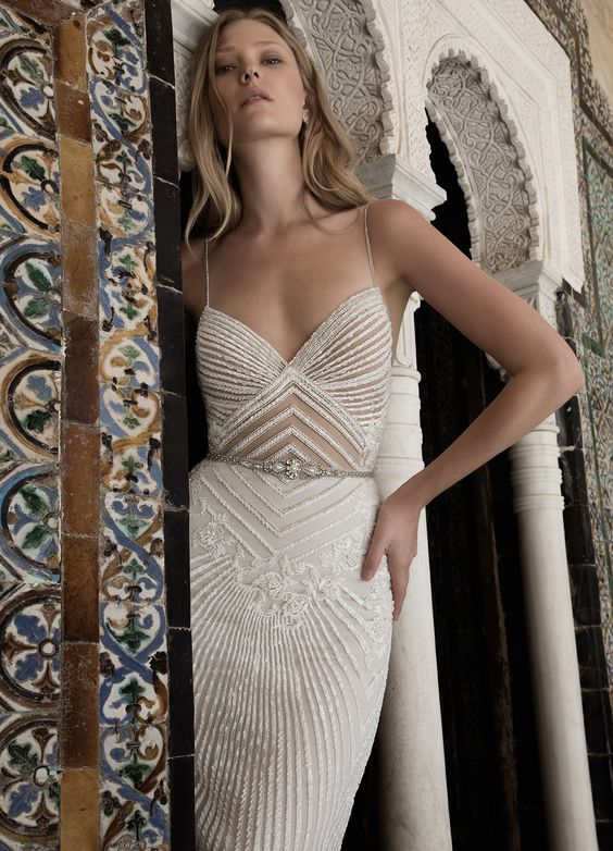 a uniquely glamorous spaghetti strap wedding dress with a feminine neckline and embellished geometric patterns