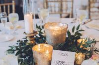 26 a cozy and simple centerpiece of marcury glass candle holders, fresh greenery and candles can be easily DIYed